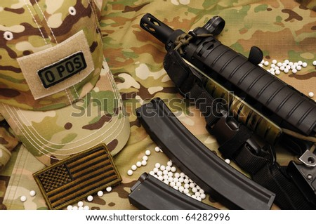 White airsoft bullets and sub-machine gun on multicam background - stock photo