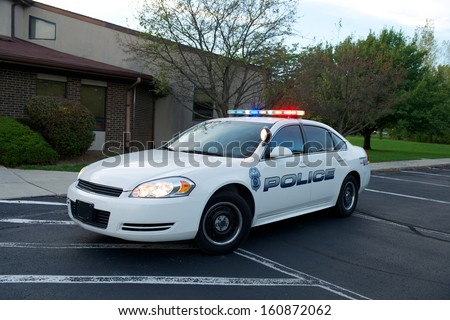 White American Police sedan with red/blue lights on.