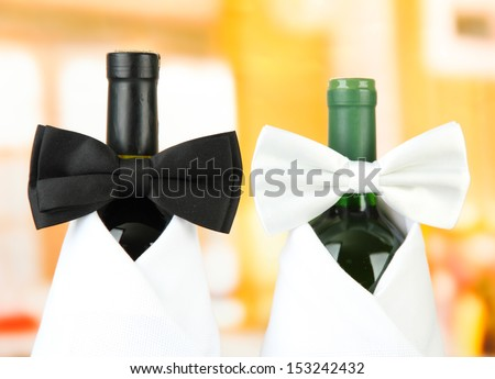 White and black  bow ties on wine bottles on bright background