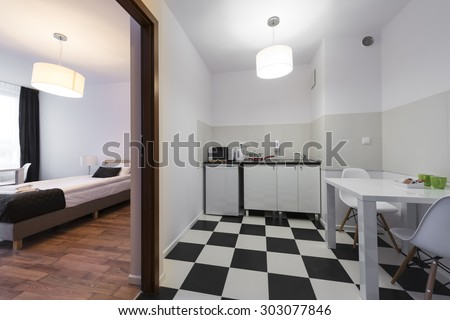 White and black small and compact kitchen end bedroom interior design - stock photo