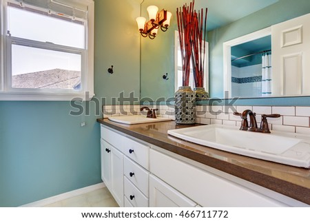 White and blue bathroom interior with one window and two sinks. Northwest, USA