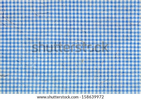White and blue checkered pattern with embedded fibers in the texture of paper.