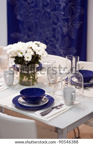 White and blue decorated dining table in restaurant - stock photo