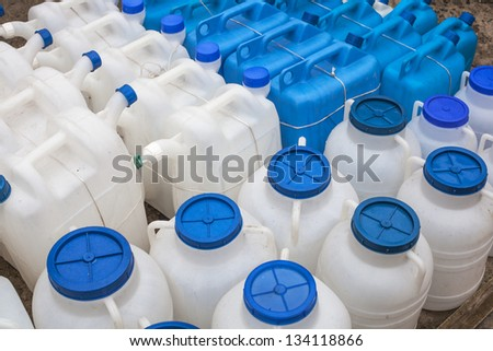 White and blue plastic gas cans (fuel container) in an open market under natural lights