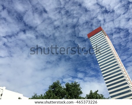 White and blue sky with hard texture cloud, high white building and green tree foreground