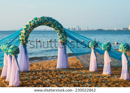 white and blue wedding arch on the beach - stock photo