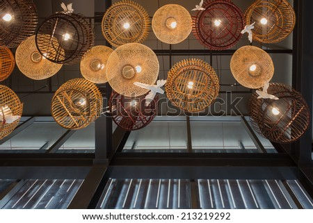 White and brown bird cage as Lamp hanging from the ceiling in the restaurant.