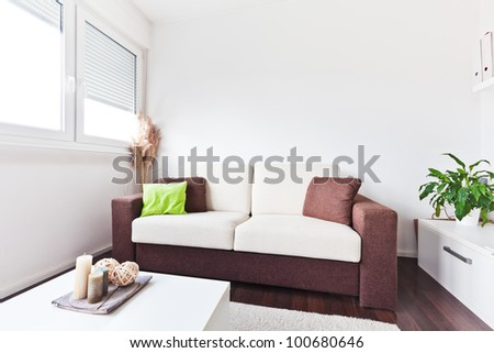 White and brown fabric sofa in the living room with brown cushions - stock photo