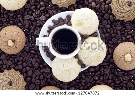 White and brown pastries with a plate of dark coffee on the center surrounded by a coffee grain - stock photo