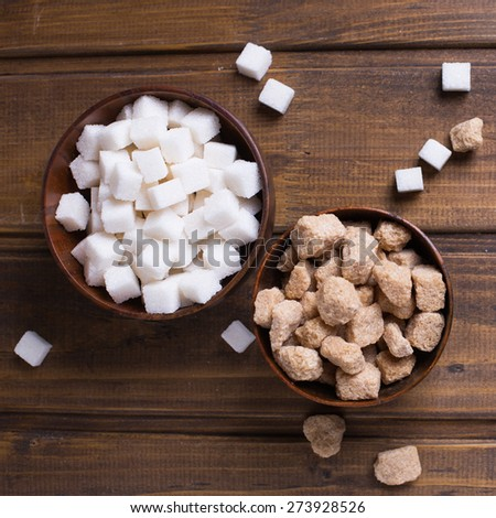 White and brown sugar cubes in bowls  on dark painted wooden planks. Selective focus.Square image.