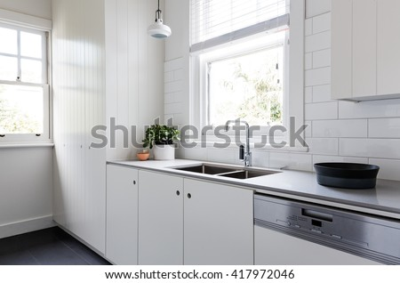 White and charcoal new renovated galley style Australian apartment kitchen - stock photo
