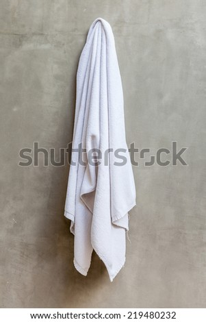 White and clean towel is hanging on the exposed concrete wall in the bathroom