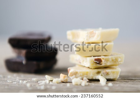 white and dark chocolate piled on a wooden table - stock photo