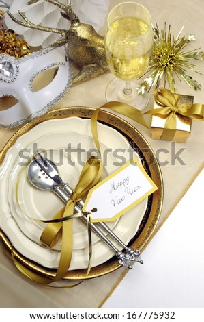 White and gold Happy New Year elegant fine dining table place setting in gold theme Christmas and New Year decorations. - stock photo