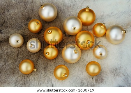 White and golden Christmas balls on a reindeer fur coat