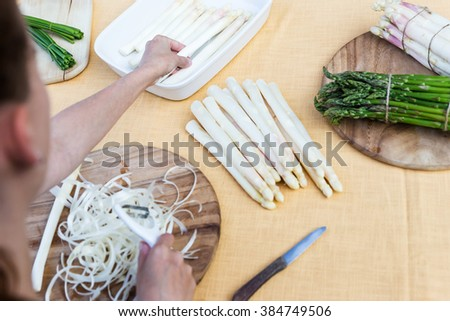 white and green asparagus on a table, woman is peeling the asparagus, topview