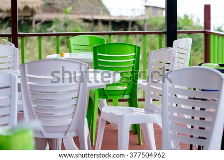 white and green plastic chairs in restaurant