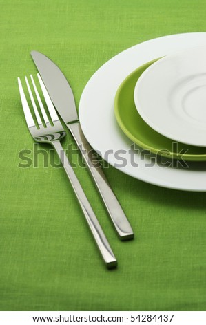 White and green plates, stainless fork and knife on green linen tablecloth. - stock photo
