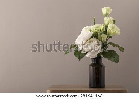 White and green roses for wedding bouquet in the flower vase on the wood table(desk) brown background in the studio.  - stock photo