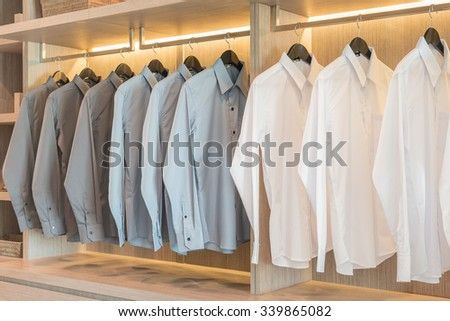 white and grey shirts hanging in wooden wardrobe - stock photo