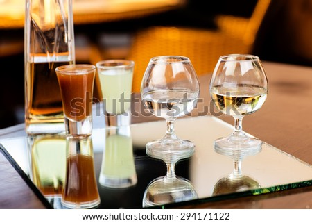 White and old Tequila shots in a bar table with bottle and lemon - stock photo