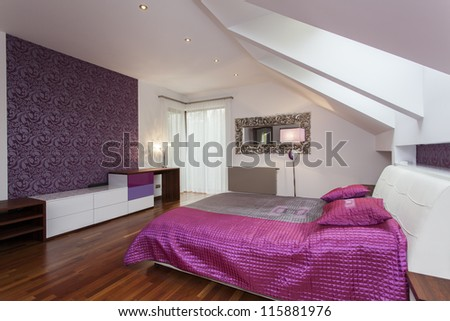 White and purple bedroom with patterned wall - stock photo
