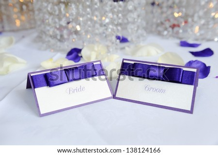 White and purple bride and groom place cards at wedding reception