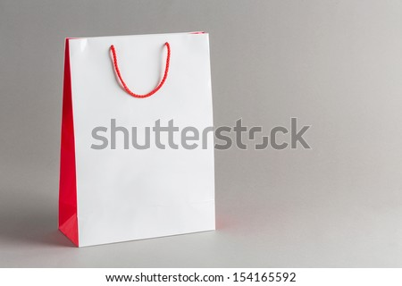 White and red color paper shopping bag isolated on gray background - stock photo