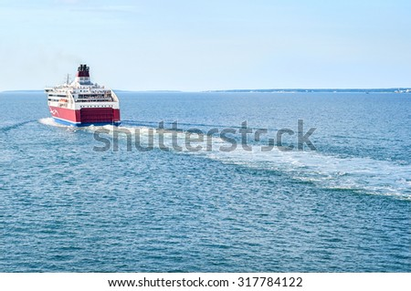 White-and-red cruise ferry sailing to the horizon in the Baltic Sea leaving the diagonal trace - stock photo