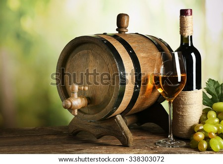 White and red grape with wine bottle near barrel on wooden table, close up - stock photo