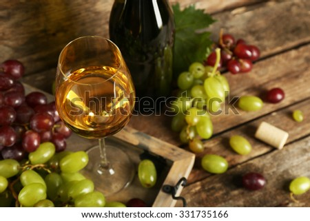 White and red grape with wine bottle on wooden background - stock photo