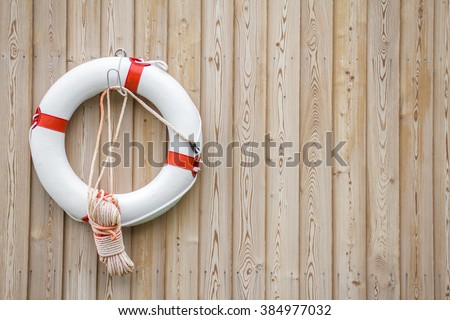 White and red life buoy on yellow wooden background. Symbol of salvation, protection and security. One life buoy hanging on wall, backdrop for card with blank place for your own text, message.Postcard - stock photo