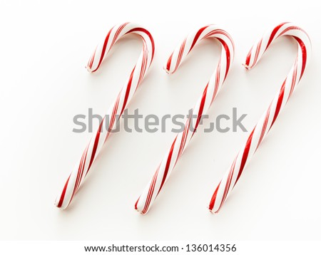White and red peppermint candy cane on white background.