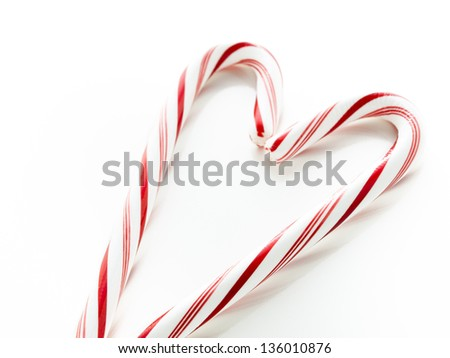 White and red peppermint candy canes forming heart shape on white background.
