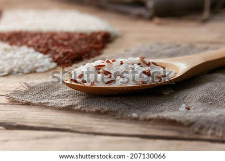 white and red rice in a wooden spoon on the sackcloth with ball of twine on an old wooden table - stock photo