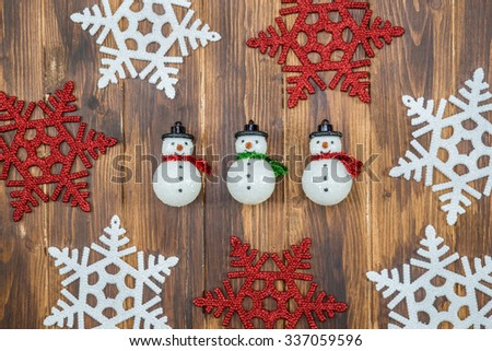 white and red shiny snowflakes and snowman decoration on wooden background