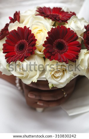 White and red wedding bouquet of roses and gerberas in the hands of the bride  - stock photo