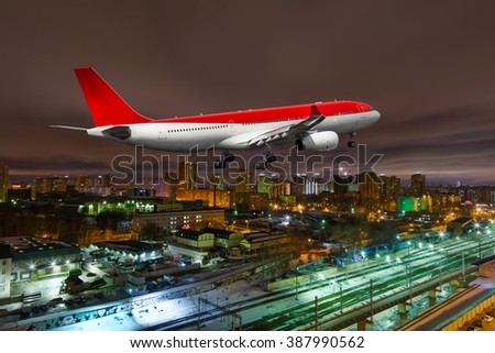 White and red wide-body passenger plane. Aircraft is flying over railways at night. - stock photo