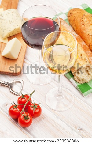 White and red wine glasses, cheese and bread on white wooden table background