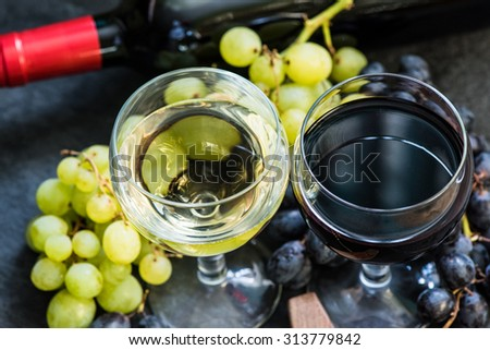 white and red wines in glasses, bottle and corkscrew overhead - stock photo