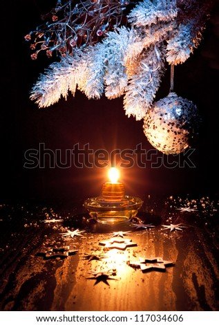 White and silver Christmas decorations, candle on a table - stock photo
