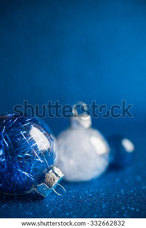 White and silver christmas ornaments on dark blue glitter background with space for text. Merry christmas card. Winter holidays. Xmas theme. - stock photo