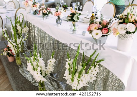 White and silver tablecloth on the wedding table - stock photo