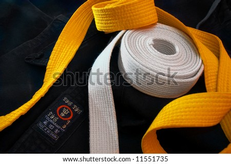 White and yellow karate belts coiled on a folded black gi