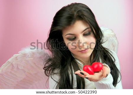 White angel girl with two red small hearts in the hand - stock photo