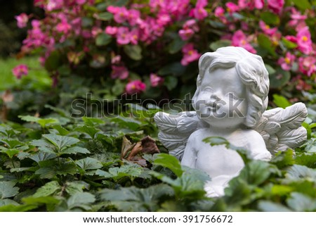 white angel in front of flowers - stock photo