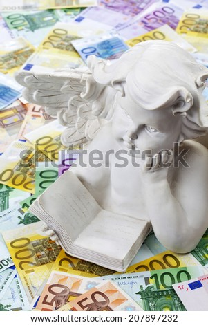 White angel sculpture on heap of euro notes - stock photo