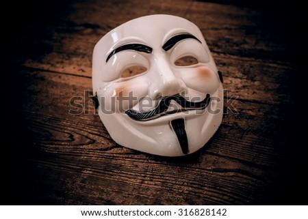 white anonymous mask on wood background - retro style - stock photo