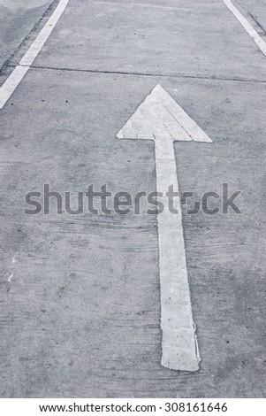 white arrow on road, direction straight. - stock photo