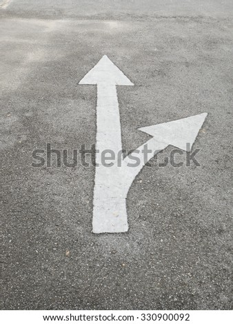 White arrow traffic sign on the road - stock photo